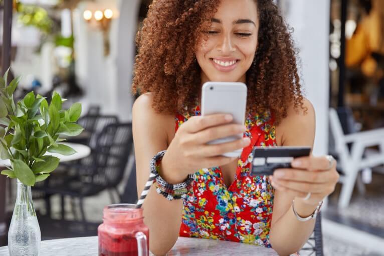 frau-mit-happy-look-hält-moderne-kreditkarte-macht-online-shopping-via-smartphone